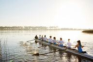 Female rowers rowing scull on sunny lake - CAIF20661