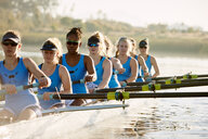 Female rowers rowing scull on sunny lake - CAIF20673