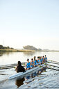 Female rowers rowing scull on sunny lake - CAIF20676