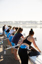 Female rowers lowering scull from lakeside dock - CAIF20679