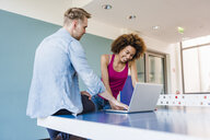 Couple looking at laptop on table tennis table - CUF09783