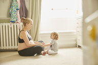 Pregnant woman and daughter in bedroom - CUF09885
