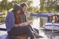 Couple eating cupcakes on canal boat - CUF09918
