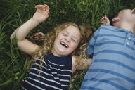 Brother and sister enjoying outdoors on green grassy field - CUF09993