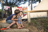 Male toddler being kissed on cheek by his big brother on campsite - CUF10041