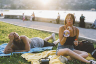 Young couple blowing bubbles on waterfront grass, Lake Como, Lombardy, Italy - CUF10092