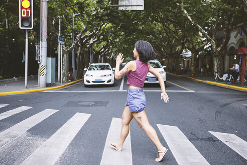 Woman marching across pedestrian crossing, Shanghai French Concession, Shanghai, China - CUF10128