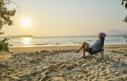 Woman on beach in deckchair looking away at sea, Florianopolis, Santa Catarina, Brazil, South America - CUF10167