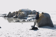 Mid adult man with dog leaning against boulder gazing at sea, Cape Town, Western Cape, South Africa - CUF10188