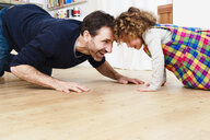 Mature man crawling head to head with daughter on kitchen floor - CUF10266