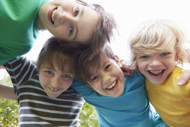 Low angle view of four boys with arms around each other in park - CUF10350