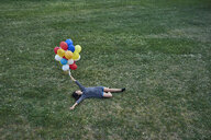 Young woman with bunch of balloons lying on a meadow - BEF00082