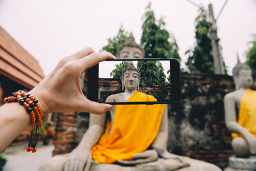 Thailand, Ayutthaya, Wat Yai Chai Mongkhon, taking a photo from Buddha with smartphone - GEMF01990