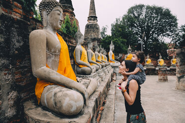 Thailand, Bangkok, Ayutthaya, Buddha statues in a row in Wat Yai Chai Mongkhon, mother and daughter in front of a buddha statue - GEMF01993