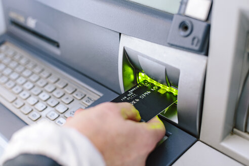 Close up of woman's hand inserting credit card into cash machine - CUF10420