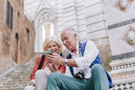 Tourist couple looking at smartphone on Siena cathedral stairway, Tuscany, Italy - CUF10423