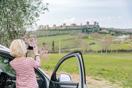 Rear view of female tourist photographing fort in landscape, Siena, Tuscany, Italy - CUF10432