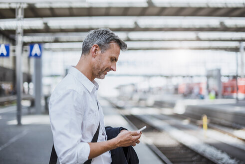 Mature man standing on station platform, looking at smartphone - CUF10438