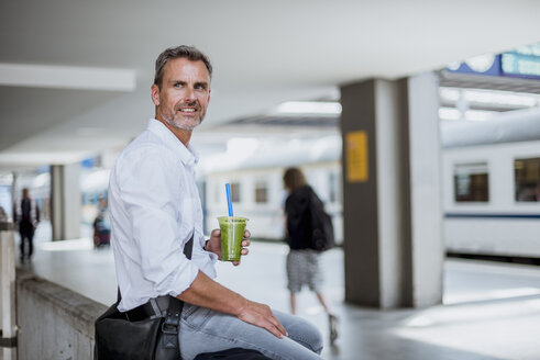 Mature man sitting on wall at station platform, waiting for train, holding healthy juice drink - CUF10441