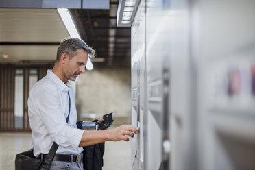 Mature man using ticket machine at train station - CUF10450