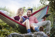 Couple relaxing in hammock, smiling, Krakow, Malopolskie, Poland, Europe - CUF10480