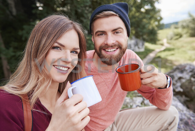 Portrait of couple holding enamel mugs looking at camera smiling, Krakow, Malopolskie, Poland, Europe - CUF10495 - Gpointstudio/Westend61