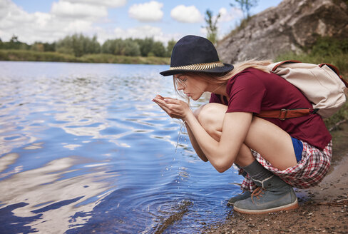 Woman crouching by waters edge scooping up water in hands, Krakow, Malopolskie, Poland, Europe - CUF10507