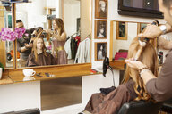 Hairdressers using curling tongs on customers long red hair in salon - CUF10559