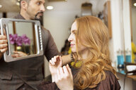 Hairdresser showing customer styled long red hair in salon - CUF10562