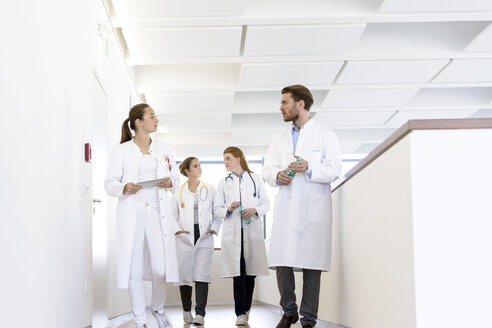 Male and female doctors walking in hospital corridor, talking - CUF10586