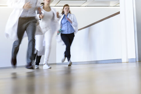 Male and female doctors running along hospital corridor - CUF10589