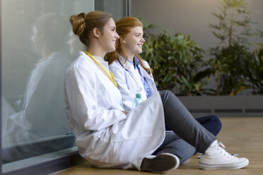 Two young female doctors sitting on floor at hospital entrance - CUF10598