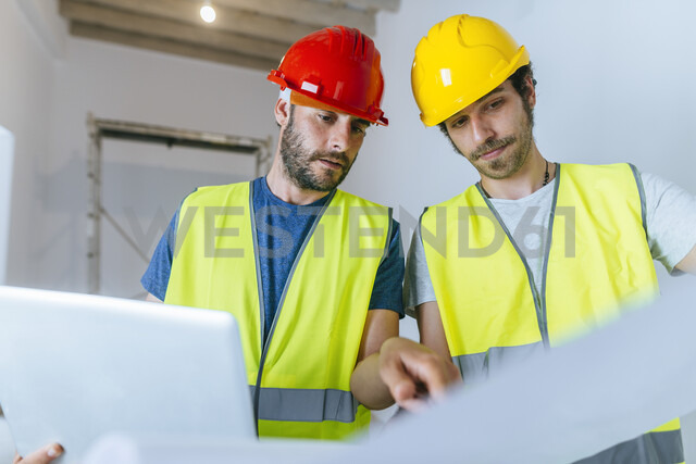 Workers working with laptop and plan on the construction site - KIJF01937