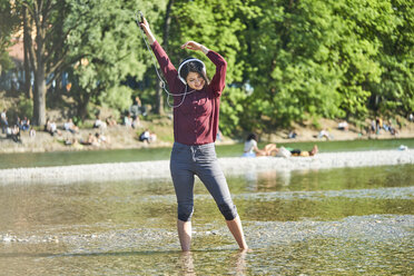 Happy young woman listening music with headphones and cell phone dancing at riverside - BEF00085