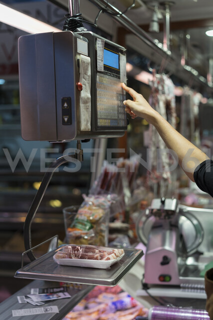 Female butcher weighing sausage on scale - AFVF00462 - VITTA GALLERY/Westend61