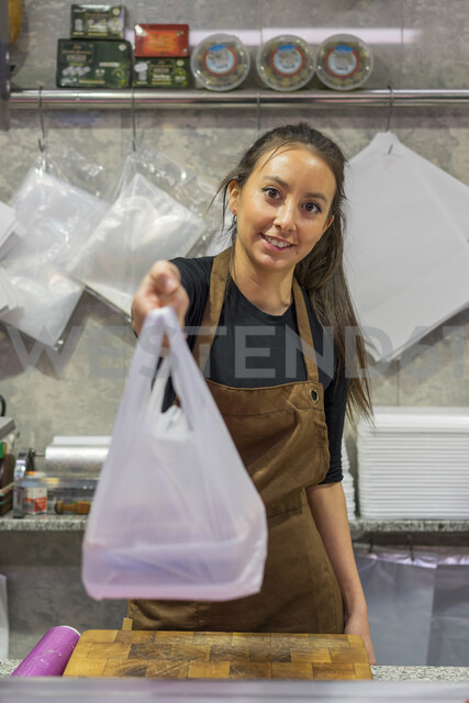 Female butcher giving plastic bag - AFVF00465