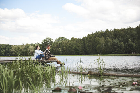 Mature couple relaxing on jetty beside lake - CUF10655