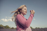 Girl in pink gazing at strawberry in field of purple wildflowers - CUF10724