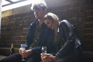 Romantic young couple sitting in bus shelter with prosecco - CUF10730