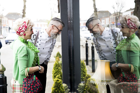 Quirky vintage couple window shopping at vintage shop - CUF10778