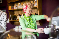 Quirky vintage mature woman working behind tea room counter - CUF10790
