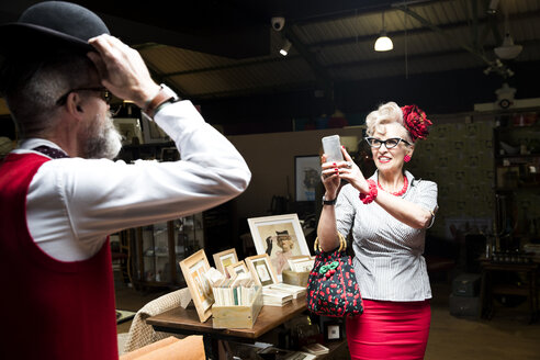Quirky vintage woman photographing boyfriend trying on bowler hat in antiques emporium - CUF10796