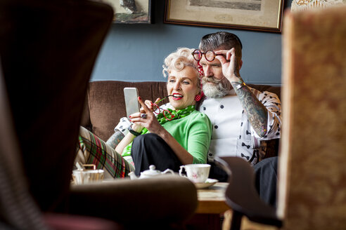 Quirky vintage couple looking at smartphone in tea room - CUF10799