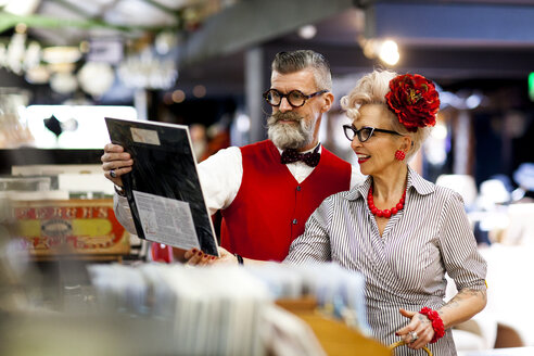 Quirky vintage couple shopping together in antiques emporium - CUF10811