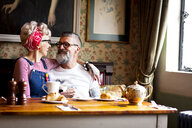 Quirky couple relaxing in bar and restaurant, Bournemouth, England - CUF10844