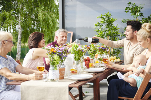 Three generation family having lunch and pouring wine on patio table - CUF10859