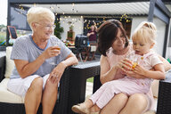 Senior and mature women with female toddler on lap at family lunch on patio - CUF10865