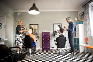Couple in vintage clothes working on customers in quirky hair salon - CUF10877