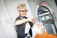 Woman working in quirky hair salon - CUF10880