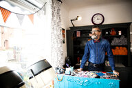 Man at reception desk of quirky hair salon - CUF10883